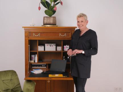 Psychotherapeutin Esther Artner in schwarz gekleidet lächelt vor ihrem Schreibtisch stehend